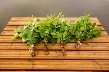Traditional Finnish bath whisks made out of fresh birch leaves and twigs on a wet jetty by the lake on Midsummer Eve 免版税图像