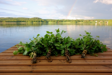 Traditional Finnish bath whisks on a jetty by the lake Foto de archivo