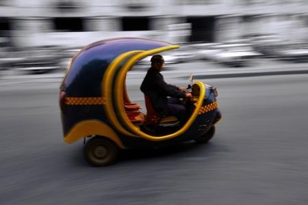 autorick: Havana, Cuba - December 19, 2013 : Three-wheeler Taxi Cocotaxi driving in the streets of Havana, Cuba in December 2013.