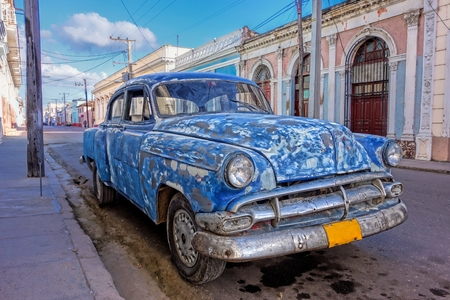 patched up: Battered, patched up and old Classic American car in streets of historic parts of Cienfuegos, Cuba at the end of the December 2013 on a sunny afternoon. Editorial