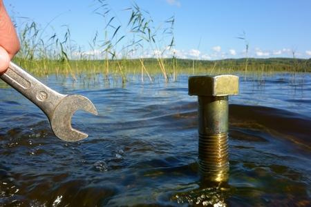 ahorrar agua: Peque�a llave de acercarse a una elevaci�n enorme perno de bronce del metal del agua del lago en un t�pico lago escandinavo limpio con la sostenibilidad, el ahorro de agua y las posibilidades conceptuales ecofriendly.