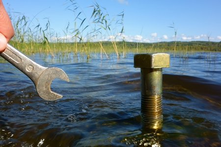 ecofriendly: Small wrench approaching  a huge brass metal bolt raising out of the lake water in a typical clean Scandinavian lake with sustainability, save water and ecofriendly concept possibilities.