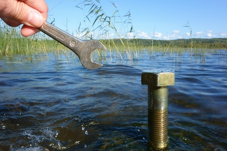 cleantech: Shiny silver wrench in mans hand and a large nut standing in clean blue water on a bright early fall afternoon in Western Finland with nature conservation, environmental concerns and green solutions concept ideas.