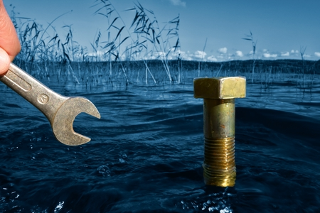 Male hand holding a wrench in front of a large bolt coming out of the lake water on a sunny Autumn afternoon in Finland with ecology, environmental protection and green concept idea.