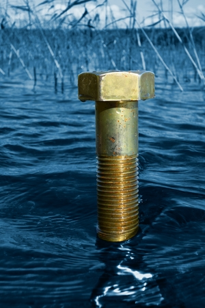 cleantech: A single massive brass bolt in lake water with deep blue selective color background