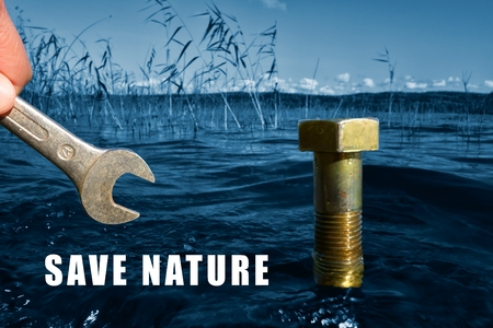 body scape: Save nature conceptual image with selective color blue lake nature and silver wrench and brass nut in the water