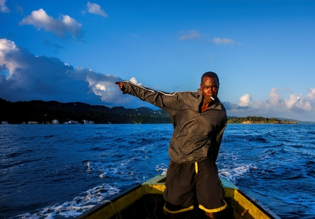 jamaican man: Port Antonio, Jamaica - December 31, 2013 - Jamaican fisherman standing in traditional wooden fishing boat and holding fishing line in his hand while trolling in the Caribbean Sea on the coast of Port Antonio, Jamaica in early morning light on New Years E