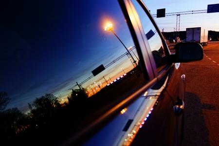 espejo: Reflexi�n de un sol y de ferrocarril patio poniendo en una ventanilla del coche en el puerto de Turku, Finlandia, con coches y camiones esperando en la cola para entrar en un ferry a Suecia.