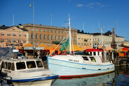 Helsinki, Finland - October 8, 2015 - Fishing boats and orange market tents at the one of the main tourist attractions of Helsinki and Finland the Market Square Kauppatori in Finnish during the annual Helsinki Baltic Herring fair Silakkamarkkinat in Finni Editorial