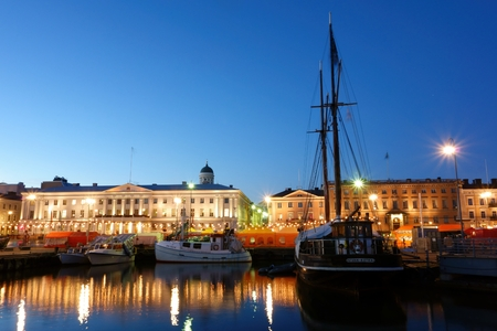 Helsinki, Finland - October 7, 2015 : Fishing boats and an old sailing boat at the Helsinki Market Square Kauppatori in Finnish with market tents on the background during the annual Helsinki Baltic Herring Fair Silakkamarkkinat in Finnish on clear early O Editorial
