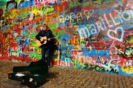 busker: Prague, Czech Republic - October 16, 2015 - A male busker performing by the colorful graffiti wall named after John Lennon on a cobblestone street in the Kampa Island of Prague, Czech Republic on mid-October afternoon in 2015