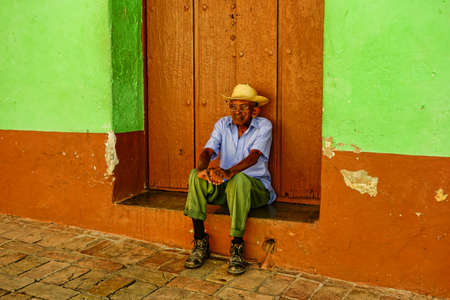 oldage: TRINIDAD - December 24, 2013 - Old Cuban man sitting in front of massive wooden door by a cobblestone street in the historic Trinidad, Cuba on Christmas Eve in 2013.
