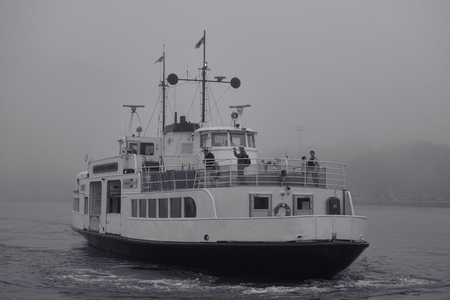 Helsinki, Finland - September 11, 2014 - Ferry to Suomenlinna fortress island in Helsinki, Finland approaching Kauppatori market place in thick fog on 11 September 2014.