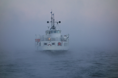 winterly: Ferry departing  Suomenlinna fortress island on Baltic sea in midst of thick sea smoke or fog on extremely cold January morning at dawn in Helsinki, Finland on 5 January 2016. Editorial