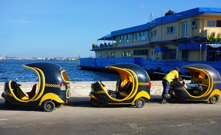 autorick: Havana, Cuba - December 26, 2013 - Three unidentified tricycle Taxis Cocotaxi and their drivers by walls of Havana harbor in Havana, Cuba on 26 December 2013.