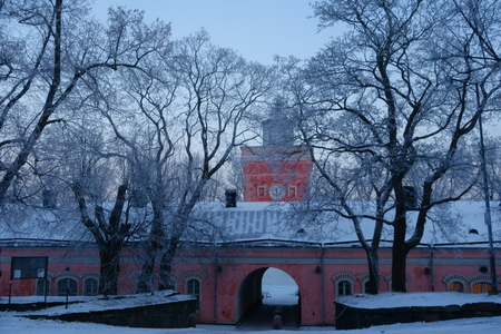 Entrance to Suomenlinna fortress island via main gate through arch in imperial Russian era historical jetty barracks and the clock tower on cold and foggy January winter morning in Helsinki, Finland.   it is one of the main tourist attractions of Helsinki