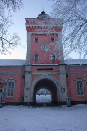 Helsinki, Finland - January 5, 2016 - Entrance to Suomenlinna fortress island via main gate through arch in imperial Russian era historical jetty barracks and the clock tower on cold and foggy January winter morning in Helsinki, Finland. Editorial