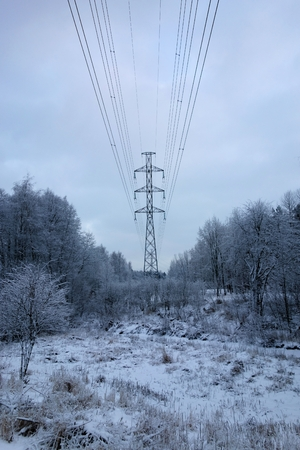 electricity grid: Power line or electricity grid in snowy city nature at suburbs of Lassila located in Western Helsinki, Finland on a winter evening on January 8, 2016. Stock Photo