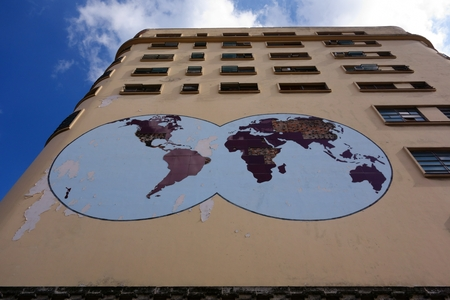 early 50s: Havana, Cuba - December 26, 2013 - Deteriorating world map on the exterior of the old Masonic Grand Lodge building that was built in early 50s in the center of Havana, Cuba against blue sky on December 26, 2013.