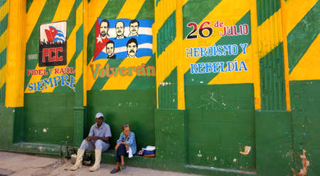 heroism: Havana, Cuba - December 26, 2013 - Unidentified Cuban male and female sitting by a colorful Mural in the wall advocating victory and heroism of the Cuban revolution 26th of July Movement painted in the exterior of a building in old Havana, Cuba on Decembe Editorial