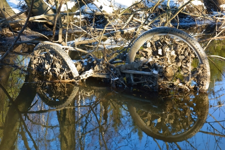 decomposing: Abandoned rusty bicycle frame and wheels in a small river in Western Helsinki, Finland in late February winter afternoon.