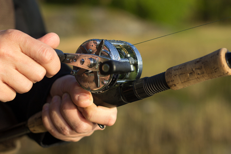 hand crank: Man fishing with reel and rod. One hand on the crank and reeling fishing line in to the round reel and other hand holding fishing rod with blurred nature background.