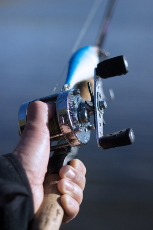 hand crank: Male hand on a spool of a round fishing reel attached to a fishing rod with fishing lure and blurred nature background. Stock Photo