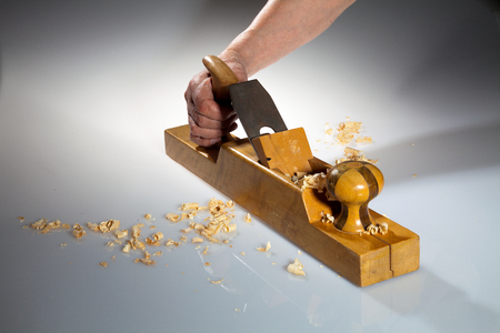 wood planer: Hand of an old man holding old wooden planer with wood chips on the foreground and background. Stock Photo
