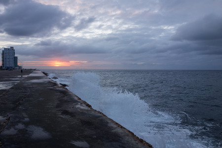 Walls of the Malecon esplanade in Havana, Cuba on dramatic evening light with storm waves bounding water on the rocks underneath the wall. Stock Photo