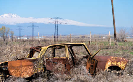Abandoned and rusty wreckage of an yellow vintage Soviet Russian car in the middle of dry hay with scenic ice top mountains and clear blue sky on the background in rural Southern Armenia in Ararat province on 4 April 2017.