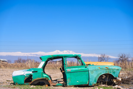 Abandoned and rusty wreck of an old green vintage Soviet Russian car in the middle of dry agricultural land with scenic snow-topped mountains and clear blue sky on the background in rural Southern Armenia in Ararat province Stock Photo