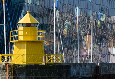 Yellow lighthouse in the Reykjavik, Iceland harbor with colorful and abstract glass exterior of the Harpa concert on the background with reflections in the windows and masts of the sailing boats in between. Stock Photo