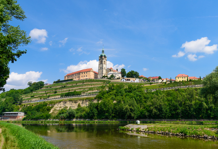 The historic Mělník castle and church tower of St. Peter and Paul at the confluence of the Vltava (Moldau) and Labe (Elbe) rivers on sunny early July afternoon in 2017. Stock Photo