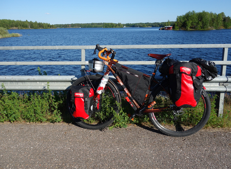 Lappeenranta, Finland – June 29, 2015: Adventure bike with mountain bike & touring bike capabilities and red panniers and other touring and camping gear attached to the bike by a lake Saimaa near Lappeenranta in Eastern Finland. Editorial