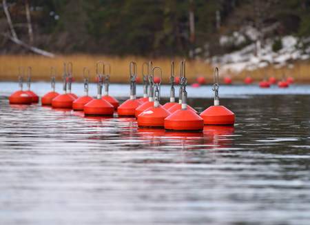 Group of bright red buoys floating in the natural harbor on the coast of Baltic Sea in Inkoo archipelago on late autumn cold and overcast day with snow on the shore after a snow storm and orange reeds in the distance horizon.