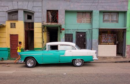 Havana, Cuba - December 19, 2013: Classic American car, unidentified girl and colourful street scene in Havana, Cuba. Editorial