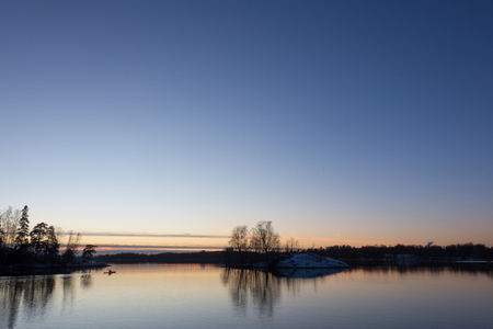 Unidentified man baddling in the Baltic Sea in cold December evening after sunset in Helsinki, Finland