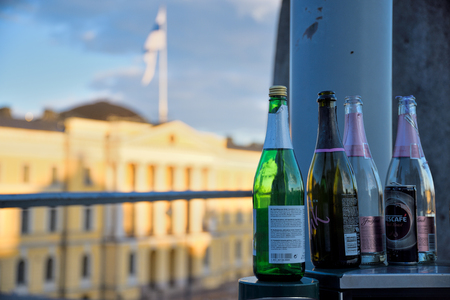 Helsinki, Finland - May 1, 2017: Empty sparkling wine bottles on top of a metallic trash bin outdoors at the Senate Square with the Finnish Government Palace and Finnish flag on the background on the evening May Day celebrations in Helsinki, Finland. Standard-Bild - 126613548
