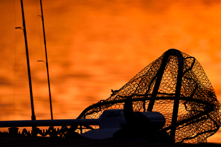 Silhouette of a trollingmotor, landing net and fishing rods on a jetty in red sunset light on late October evening in Southern Finland.