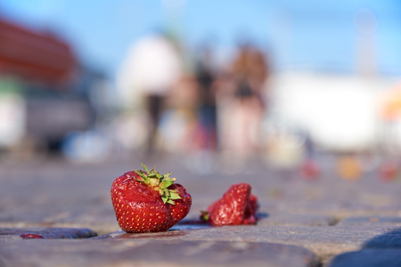 Two dropped and slightly damaged strawberries on the cobblestone ground at the Market square in center of Helsinki on a hot July evening. Stock Photo