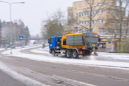 Helsinki, Finland - November 23, 2017: Winter road maintenance truck spreading de-icing or road salt on a icy and snowy street in Helsinki, Finland for creating much more safe driving conditions. Standard-Bild - 126613594