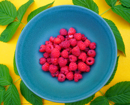 Plateful of fresh Finnish raspberries served on blue plate on yellow table with green raspberry leafs for decoration. Stock Photo