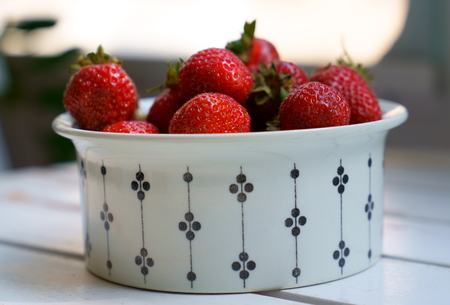 Fresh red strawberries in a white cup on a wooden table on summer afternoon on balcony