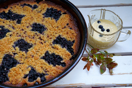 Blueberry pie and custard on a white wooden table with blueberry leaves for decoration Stock Photo