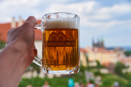 Prague, Czech Republic - July 5, 2017: A fresh pint of Czech craft beer on a terrace in Hrad�any (the historic Castle District of Prague, Czech Republic) with many of the Prague's landmarks appearing on the background on sunny summer afternoon. Standard-Bild - 126613632