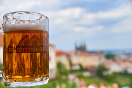 Prague, Czech Republic - July 5, 2017: A fresh pint of Czech craft beer on a terrace in Hrad�any (the historic Castle District of Prague, Czech Republic) with many of the Prague's landmarks appearing on the background on sunny summer afternoon. Standard-Bild - 126613633