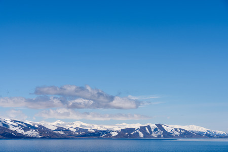 Alpine lake Sevan covered partly by ice on sunny April afternoon