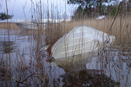 Overturned rowboat partly under flood water due to an extraordinary high sea water level at the Baltic Sea during a severe Autumn storm in Southern coast of Finland on November 10, 2017. Stock Photo