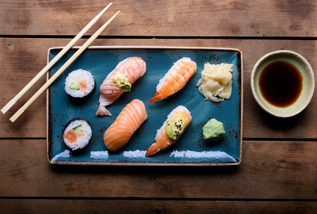 Blue plate with selection of sushi, chopsticks and soy sauce on a vintage wooden chest