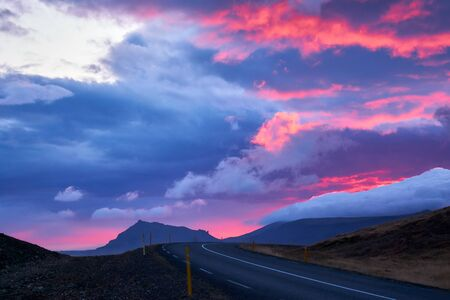 Curved road in Snaefellsnes, Western Iceland at sunset time with dramatic light, sky, clouds and colours behind mountains Standard-Bild - 131867256
